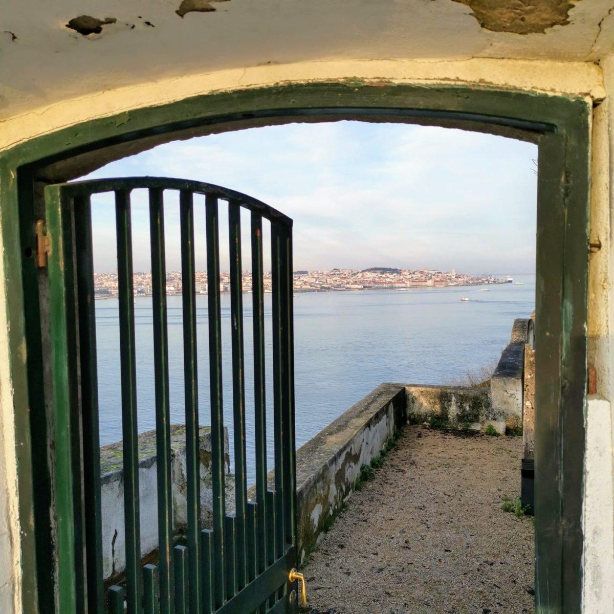 Blick durch ein Tor beim Casa de Cerca in Almada auf Lissabon